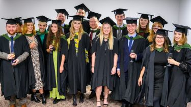 MA Journalism students in their graduation gowns pose for a group photo.