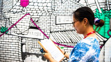 Student making notes in front of colourful street art