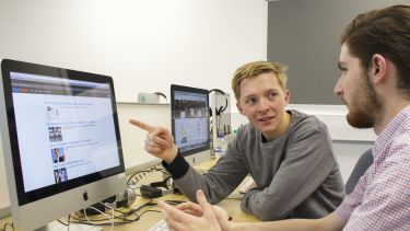 An undergraduate student discussing news. He is pointing at his computer screen.
