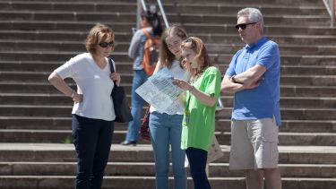 A student ambassador gives directions to a family outside Firth Court.