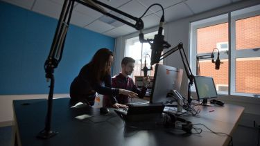 Two students using radio broadcasting equipment.