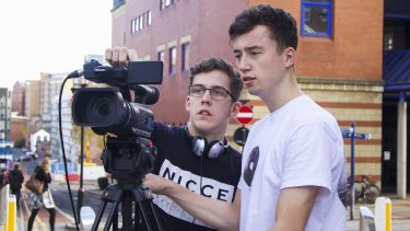 Two undergraduate students filming outside The Diamond.