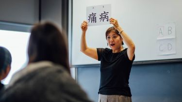 A lecturer showing students a card with two Chinese characters on