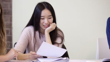 A student smiling and looking down at her notes in a seminar