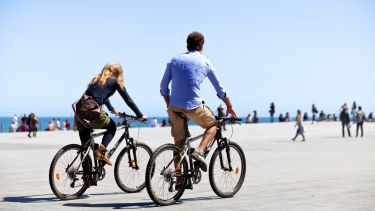 Two people cycling on sea front