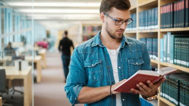 Postgraduate student reading a book stood up in a library