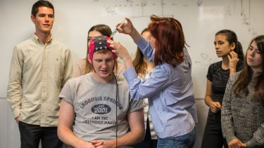 Lecturer demonstrating an EEG is a test to a class. A student wears a headpiece used to evaluate the electrical activity in the brain