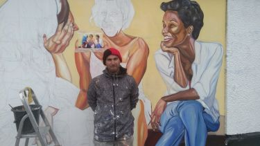 Italian muralist Jupiterfab stands against a half-finished mural of women talking