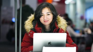 An Information School student with her laptop smiles at the camera.
