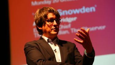 Former Guardian newspaper editor Alan Rusbridger giving a talk. He is in front of a presentation.