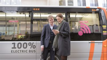 Man and woman stood in front of an electric bus looking at the woman's phone