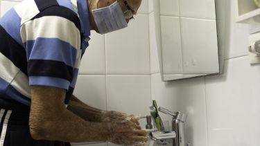 An older man washing his hands whilst wearing a face mask due to coronavirus
