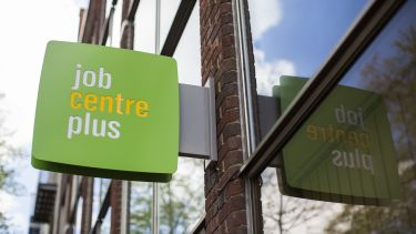 Picture of the Job Centre Plus sign attached to a building. The sign is green with white and yellow text.