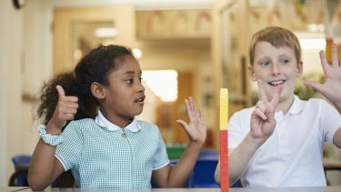 Two primary school-aged children counting on their fingers