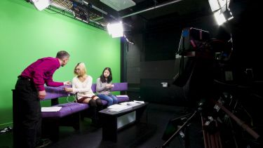 Students in the Journalism Studies TV studio preparing to present a broadcast
