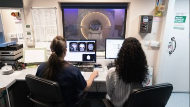 A student and doctor looking at an MRI scan on a computer screen