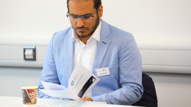 A postgraduate research student reading a brochure at the postgraduate research conference.