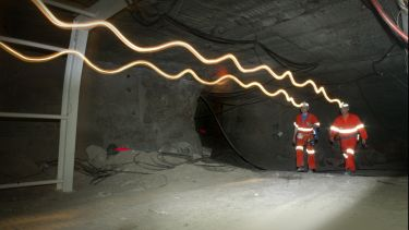 Researchers  walking through an underground tunnel at Boulby Underground Laboratory. Lightwaves coming from their head torches are visible