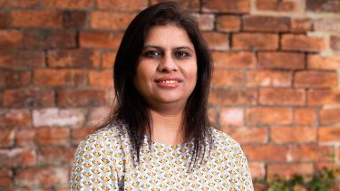 A photo of Dr Parveen Ali in front of a brick wall - image