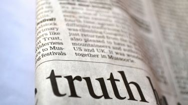 Section of newsprint with the word 'truth' in a headline