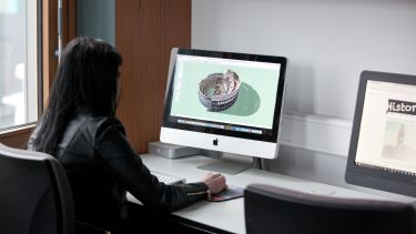 A postgraduate history student viewing a rendering of a castle on a Mac computer.