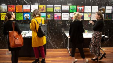 An image of visitors looking at display cases of a Library exhibition.