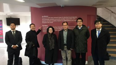 Members of AREC stood together in front of a wall sign about the centre's mission and vision
