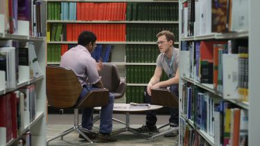 An image of seated students chatting in the Health Sciences Library.