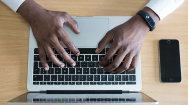 A person's hands typing on a laptop
