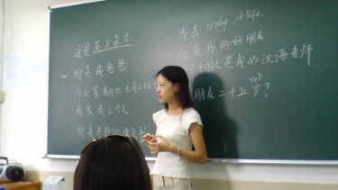Chinese Mandarin teacher in front of a blackboard in a classroom
