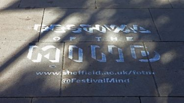Festival of the Mind logo spray-painted in white onto paving stones