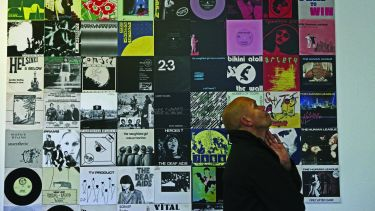 A man standing facing away from the camera in front of a wall of vinyl record covers