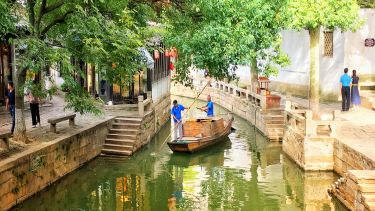A small boat on a little river going through an urban area in Suzhou, china