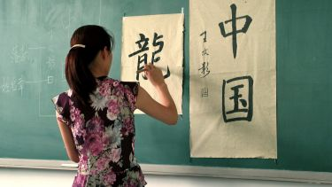 Student writing Chinese on a wall