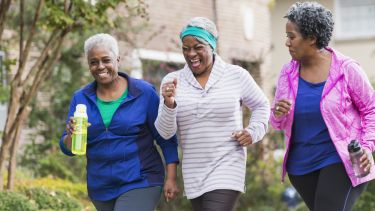 A group of three senior African America women exercising together, jogging or power walking along a sidewalk in a residential neighborhood. They are having fun, laughing.