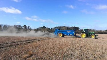 A tractor spreads rock dust on a field