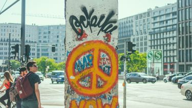 Piece of the Berlin Wall with an orange peace sign spray painted on it