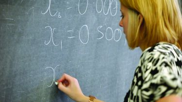 A maths student writing equations on a blackboard