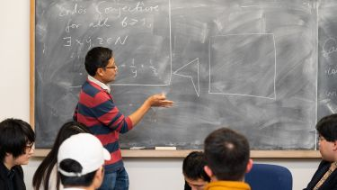 A maths lecturer at a blackboard