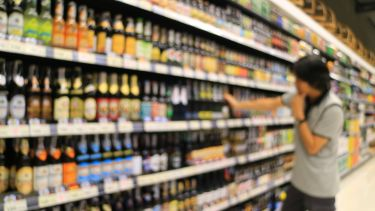 A stock image of a person browsing the alcohol aisle in a supermarket.