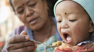 Outdoor image at day time of Asian woman feeding food to her grandson. The little child is opening his mouth wide to eat his lunch fed by his grandmother. Two people, Head and shoulder, horizontal composition and selective focus.