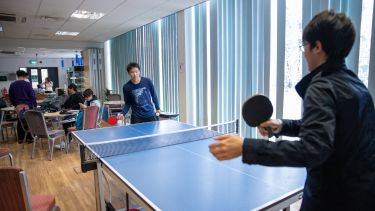 Two students play table tennis in the ELTC common room