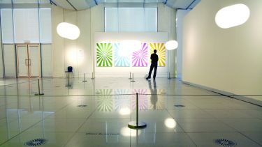 A silhouette of a man looking at a set of four graphic prints in an art gallery.