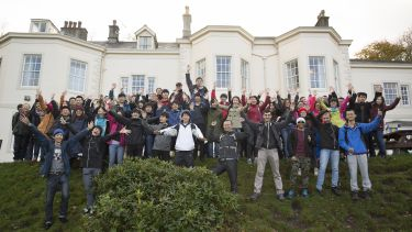 Large group of students pose outside hotel in the Lake District