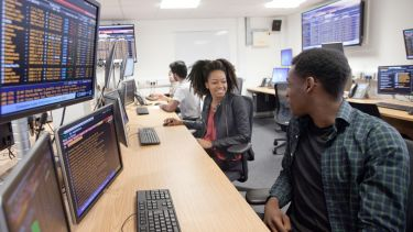 Students sitting at desks, using financial software in the Management School Trading Room