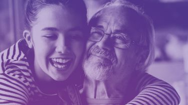 A girl is hugging an older man. They are both smiling. The image has a purple-blue filter
