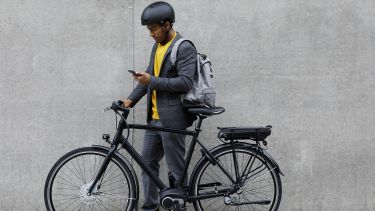 Man with an ebike stood by a concrete wall looking at his phone