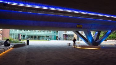 The refurbished concourse on campus. Taken from underneath the concourse, the photo shows the blue neon lights on the ceiling and yellow neon lights around the bottoms of seating areas.