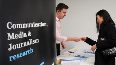A delegate is welcomed at a conference with the Communication, Media and Journalism research group
