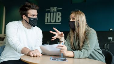boy and girl sat in edge hub with face masks on